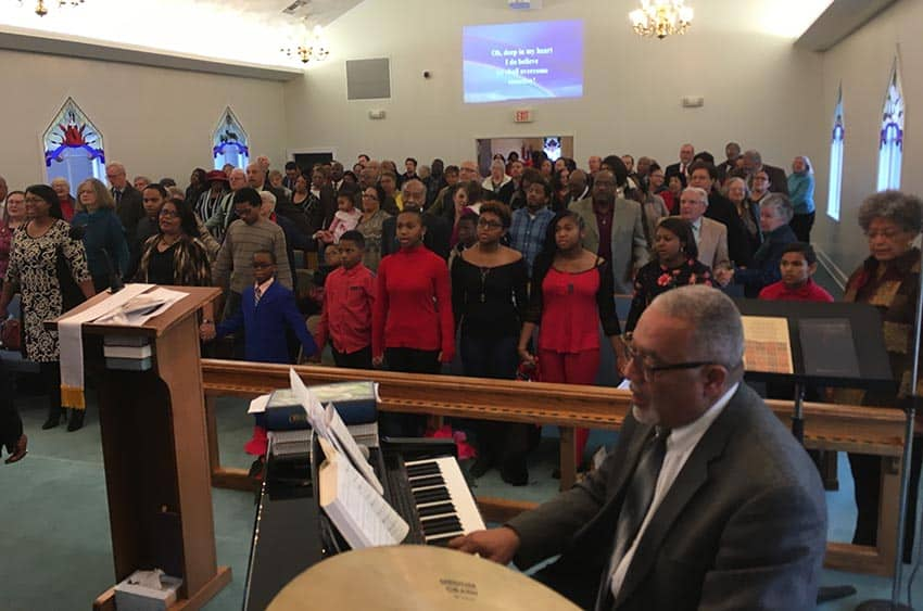 """Glen Holmes, keyboardist (foreground) and attendees singing """"We Shall Overcome."""" (photo courtesy of James C. Klagge)"""
