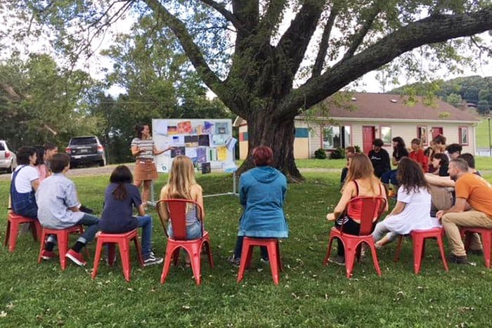 Students take advantage of good weather to meet under the maple tree outside the school which is pictured in the background (submitted by Springhouse Community School)