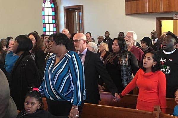 """Attendees singing """"We Shall Overcome"""" (photo by James C. Klagge)"""