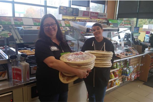 Katie Collins (right) of NRCA receives pizza from 7-Eleven Radford employee Jan Blackburn.